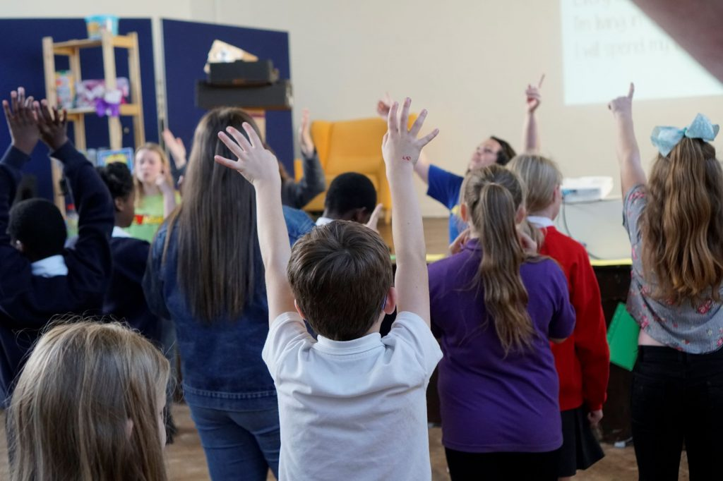 Children are seen with their hands raised, dancing in a worship song.
