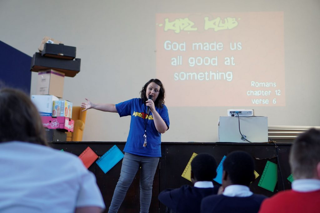 A team member talks to children as they listen